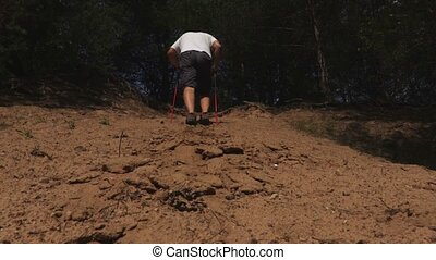 Hiker with walking poles climb a sandy slope
