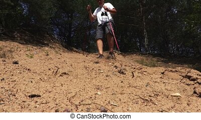 Hiker with walking poles on sand slope