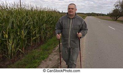 Hiker with walking sticks near corn field
