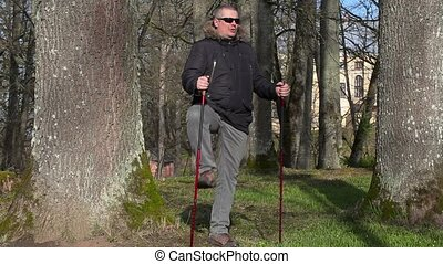 Hiker with walking sticks warm up in the park