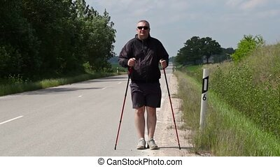 Hiker with walking sticks warm up on the highway
