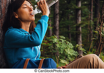 Hiker woman drinks water - Hiker young woman rests near a...