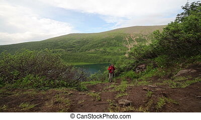 Hiker woman is walking mountain, - Hiker woman walking on...