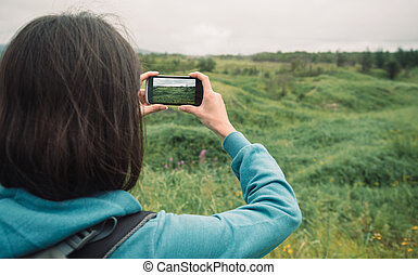 Hiker woman photographs the summer landscape - Hiker young...
