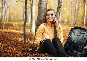 Hiker woman resting and talking on mobile phone
