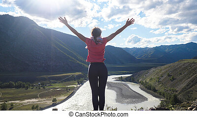 Hiker woman standing on top of a mountain with hands rised up. Back view, travel and recreation.