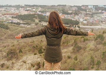 Hiker woman standing with raised arms outdoor