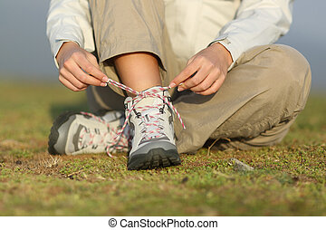 Hiker woman tying shoelaces of boots