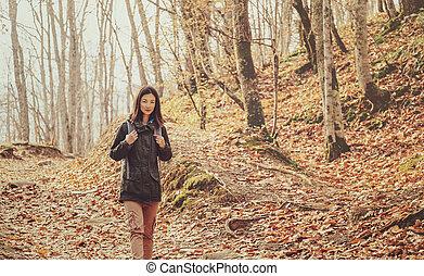 Hiker woman walking in autumn forest