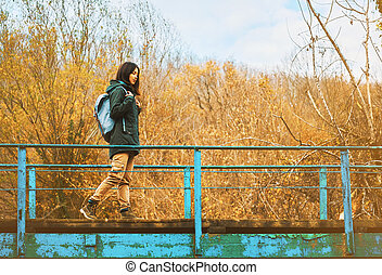 Hiker woman walking on bridge outdoor