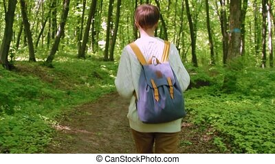 Hiker woman with backpack walking in the forest. Travel concept.