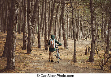 Hiker woman with bike in the forest