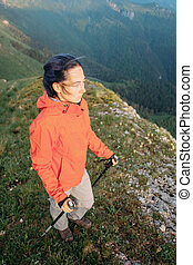 Hiker woman with trekking poles in mountains.