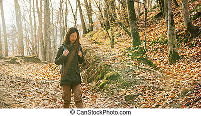 Hiker young woman walking in autumn forest