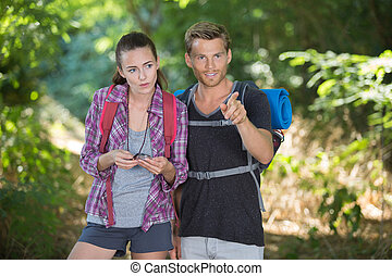 hikers backpackers couple looking at compass