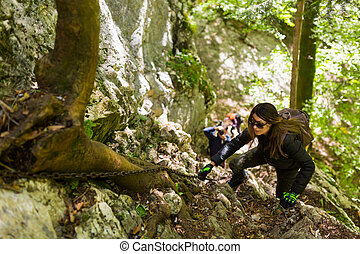 Hikers climbing on mountain wall