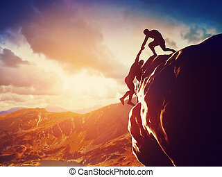 Hikers climbing on rock, mountain at sunset, one of them...