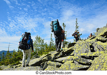 Hikers climbing up the mountain. - Group of tourists are...