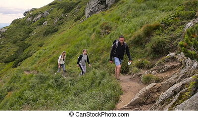 Hikers hiking in beautiful landscape. Man and women trekking walking with backpacks in mountains