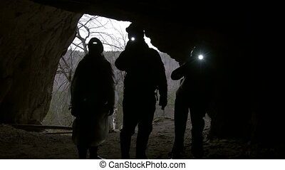 Hikers in helmets silhouettes enters to explore the dark...