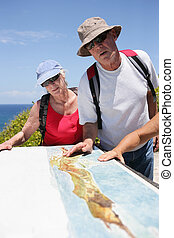 Hikers looking at a map by the coast