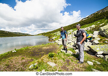 Hikers nearby a lake in the mountains