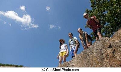 Hikers on mountain summit enjoying panoramic view - Cheerful...