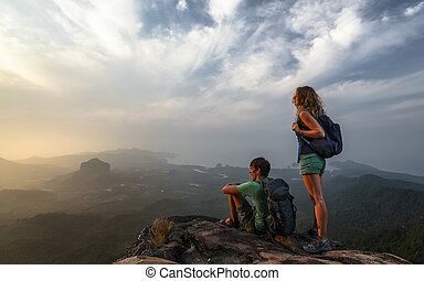 Couple of hikers with backpacks watching sunrise with valley view