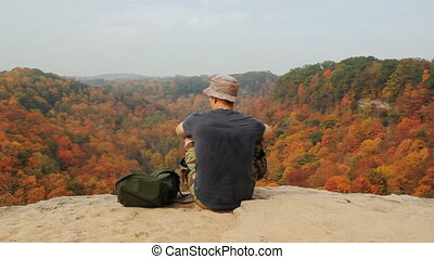 Man rests after hiking to top of cliffs. View of autumn forest below. Dundas, Ontario, Canada.