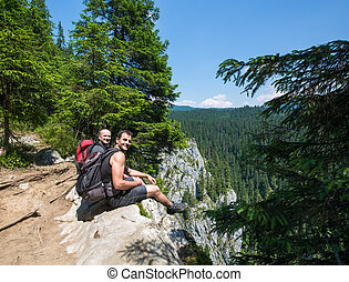 Hikers sitting on the edge of a very high cliff
