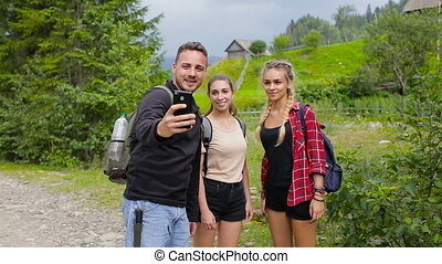 Hikers taking selfies in the mountains on the road