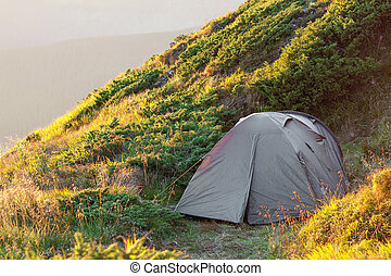 Hikers tent in mountains on a sunny summer evening