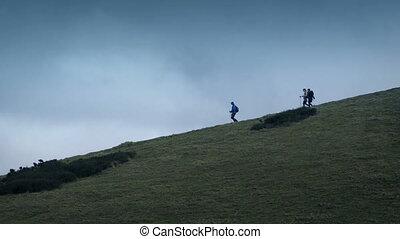 Hikers Walk Down Hillside - People walking down hill on...
