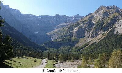 Hikers walk towards the Cirque de Gavarnie. Pyrenees mountains, France.
