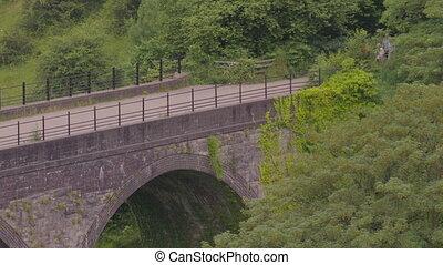 Medium high angle still shot of hikers walking across Headstone Viaduct, Monsal Trail, Peak District UK