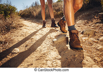 Hikers walking on the country path - Close-up of legs of...