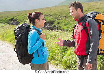 Hikers with backpacks chatting together