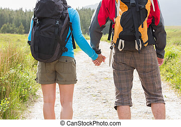 Hikers with backpacks holding hands