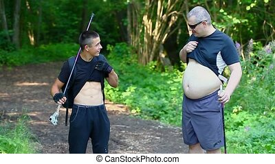 Hikers with six pack and overweight in forest on trail
