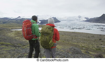 Hiking adventure travel people on Iceland living active healthy lifestyle wearing jackets and backpacks, on Iceland by glacier and glacial lagoon / lake of Fjallsarlon Vatnajokull National Park.