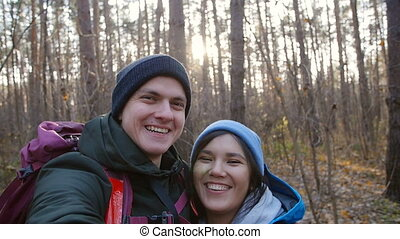 Hiking and Backpacking concept. Young happy couple with backpacks in the forest and making selfie