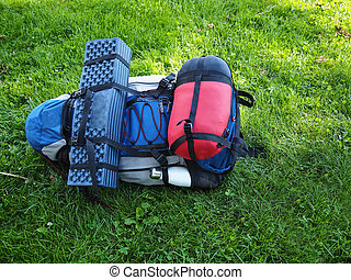 Hiking and travel backpack and gear on green grass