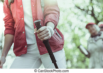 Hiking as a lifestyle. Woman holding a trekking pole while hiking