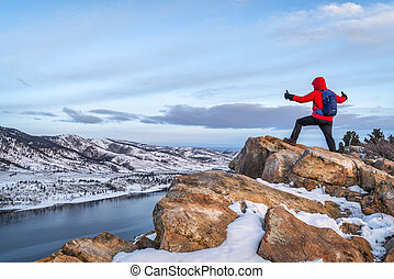 hiking at dawn over frozen mountain lake - male hiker ...