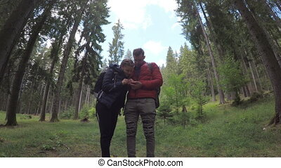 Hiking backpackers couple in forest looking at gps map using...