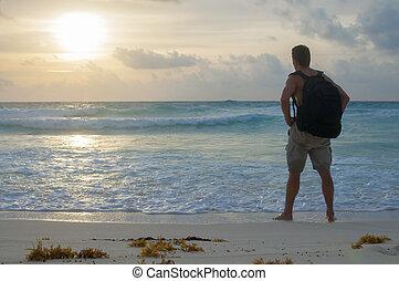 Hiking beach at sunrise - Adventurous Caucasian hiker stands...