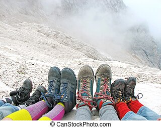 eight hiking boots of a family rest on the Italian Alps