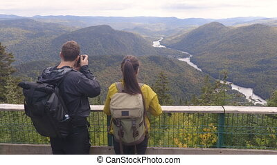 Hiking couple with backpacks in Quebec National Park in Autumn season taking photos in Canada forest travel lifestyle. Tourists looking at view of Jacques Cartier National Park.