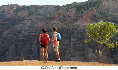 Hiking couple looking at view during hike in Waimea Canyon ...