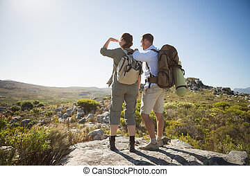 Hiking couple looking out over country terrain on a sunny ...